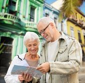 family, age, tourism, travel and people concept - senior couple with map over latin american city street background