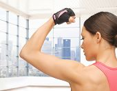 people, fitness, sport and bodybuilding concept - close up of sporty young woman flexing her biceps over gym or home background