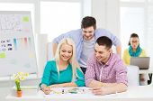 education, interior design and office concept - smiling interior designers with color samples and blueprint in office