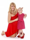 Alluring very fashionable mother and daughter in a red dress.