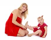 Charming fashionable mom puts on her little shoes adorable daugh