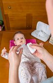 Hands of mother pouring serum to clean baby eyes