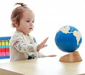 very small but serious little girl spinning globe hand.