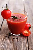 Tomato juice in glass with pepper and rosemary on wooden planks background