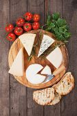 Assorted cheese on wooden platter, rich and healthy snack or breakfast