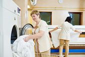 Hotel linen cleaning services. Woman operating with industrial washing machine