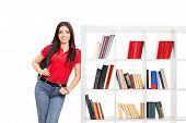 Female student leaning on a bookshelf isolated on white background