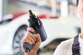 car mechanic with tool in front of luxury car in auto workshop