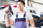Asian Chinese car mechanic with tool in front of luxury car in auto workshop