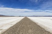 Old closed road crossing vast salt flat dry lake in California's Mojave National Preserve.