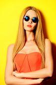 Beautiful elegant lady over bright yellow background. Beauty, fashion concept. Optics.