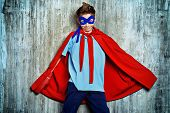 A boy teenager in a costume of superhero.