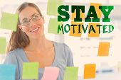 Female artist looking at colorful sticky notes against stay motivated