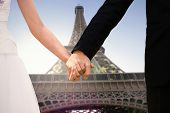 Mid section of newlywed couple holding hands in park against eiffel tower