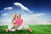 Happy couple sitting and holding heart pillow against sunny day by the river