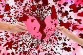 Hands holding two halves of broken heart against digitally generated girly heart design