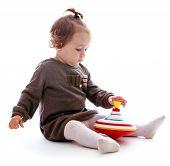 foto of dreidel  - Pretty little girl sitting on the floor and playing dreidel - JPG