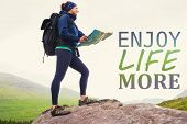 Woman standing on a rock holding map against enjoy life more