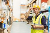 Portrait of warehouse worker with clipboard in a large warehouse