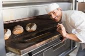 Happy baker by open oven in the kitchen of the bakery