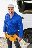 Smiling handyman looking at camera in front of his van