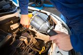 stock photo of torches  - Mechanic examining under hood of car with torch at the repair garage - JPG