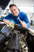 Mechanic smiling at the camera fixing engine at the repair garage