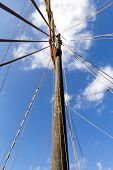 stock photo of mast  - View up a mast of an old sailing boat against slightly cloudy sky - JPG