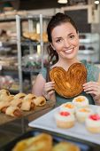Pretty brunette holding heart shape pastry at the bakery