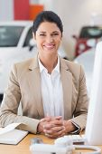 Happy businesswoman working at her desk at new car showroom