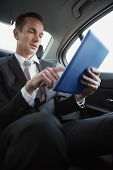 Handsome businessman using his tablet pc in his car