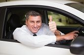 Smiling man sitting in his car giving thumbs up at new car showroom