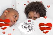 Happy couple lying in bed under the duvet against happy valentines day