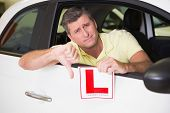 Man gesturing thumbs down holding a learner driver sign at new car showroom