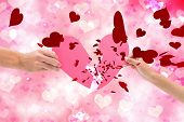 stock photo of broken heart  - Hands holding two halves of broken heart against digitally generated girly heart design - JPG