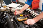 Mechanic using diagnostic tool on engine at the repair garage