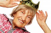 Senior woman wearing crown doing funky action isolated on white background