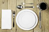 Empty plates with a white napkin dining room, cutlery set and a wine glass on a wooden background