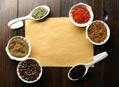 Different kinds of spices in bowls and spoons on blank paper sheet on wooden background