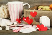 Heart shaped teabag tags, macaroons and cup of tea on wooden background