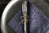 Silverware tied with rope on napkin and metal tray background