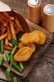 Breaded fried chicken nuggets and potatoes in paper bag with asparagus on cutting board and rustic wooden background