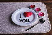 Cookie in form of heart on plate with inscription I Love You, and candles on napkin and wooden table background
