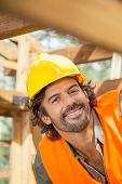 Portrait of smiling construction worker in incomplete wooden cabin at site