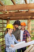Portrait of smiling male architect examining blueprint with colleagues in wooden cabin at site