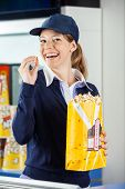Portrait of cheerful female worker eating popcorn from paperbag at cinema concession stand