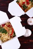 Chinese noodles in takeaway boxes on bamboo mat background