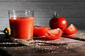 glass of tomato juice with spices and fresh tomatoes on wooden table. With dark background