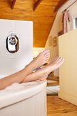 Bathtime. Girl's feet sticking out from bath tub.