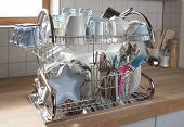 Dishes drying on a metal dish rack in a kitchen